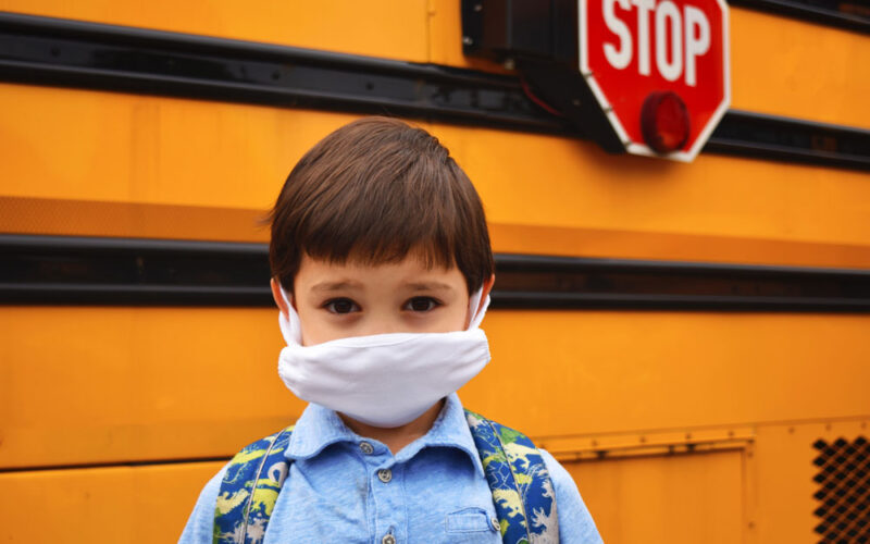 Child with mask on in front of school bus