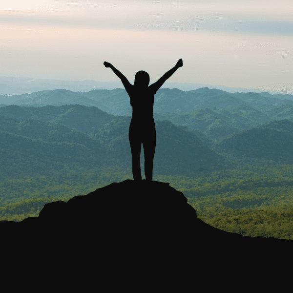 silhouette of a woman standing on a mountain with arms raised in triumph