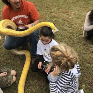 Lowcountry Exotics shares a fascinating snake with a group of children.