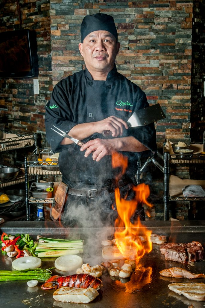 Japanese hibachi grill or teppanyaki chef in front of flaming grill