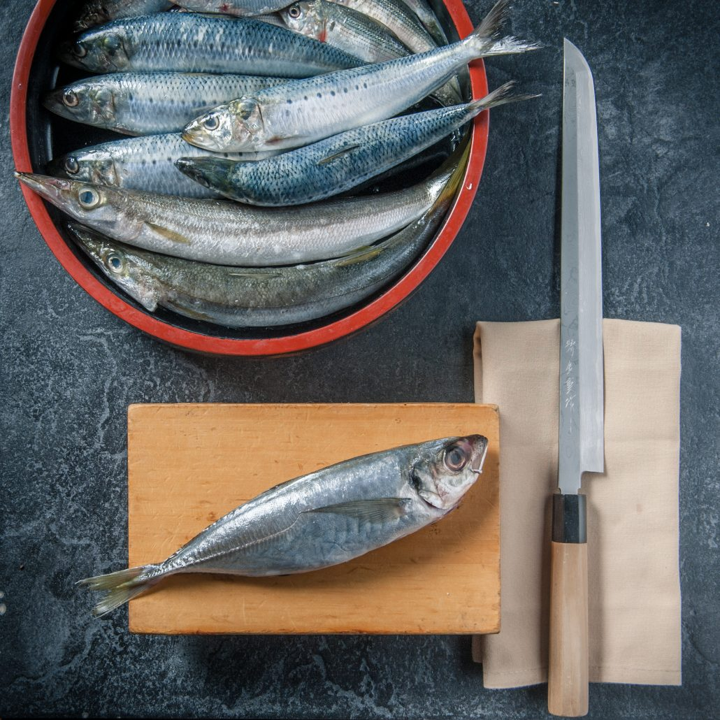 Fresh mackeral and hocho japanese knife on sushi master cutting board