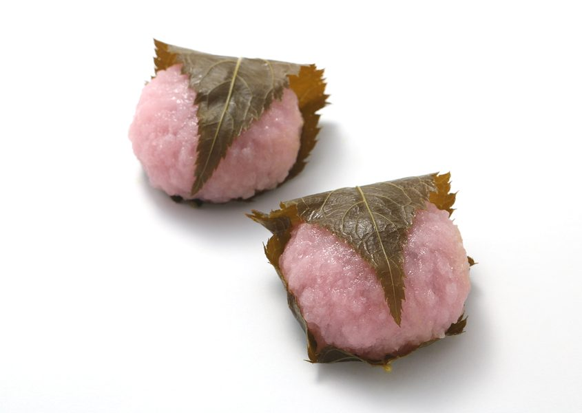 Sakuramochi, japanese confectionery wrapped in a preserved cherry on white background.
