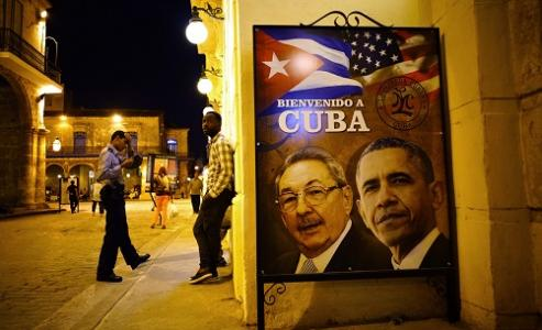 """A poster features portraits of Cuba's President Raul Castro, left, and U.S. President Barack Obama and reads in Spanish """"Welcome to Cuba"""" outside a restaurant in Havana, Cuba, Thursday, March 17, 2016. Obama is scheduled to travel to the island on March 20, the first U.S. presidential trip to Havana in nearly 90 years. (AP Photo/Ramon Espinosa)"""