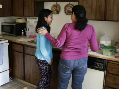 In this photo taken March 31, 2016, Teresa Garcia, right, helps her daughter, Alondra Miranda, 11, get ready for school at their home in Federal Way, Wash., south of Seattle. Garcia, who has spent 14 years in the United States illegally after staying beyond the expiration of her tourist visa in 2002, is one of millions who could be affected when the political fight over immigration comes to the U.S. Supreme Court on Monday, April 18, 2016 as the court weighs the fate of Obama administration programs that could shield roughly 4 million people from deportation and grant them the legal right to hold a job. (AP Photo/Ted S. Warren)