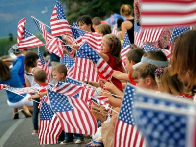 People wave flags as the Independence Day parade rolls down Main Street, Friday, July 4, 2014, in Eagar, Ariz. The Northern Arizona town celebrates the Fourth of July annually with a parade and fireworks. (AP Photo/Matt York)
