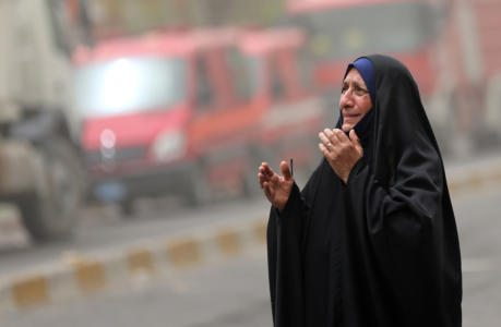 An Iraqi woman grieves at the scene of a deadly suicide a car bomb at a commercial area in Karada neighborhood, Baghdad, Iraq, Sunday, July 3, 2016. Dozens of people have been killed and more than 100 wounded in two separate bomb attacks in the Iraqi capital Sunday morning, Iraqi officials said. (AP Photo/Hadi Mizban)