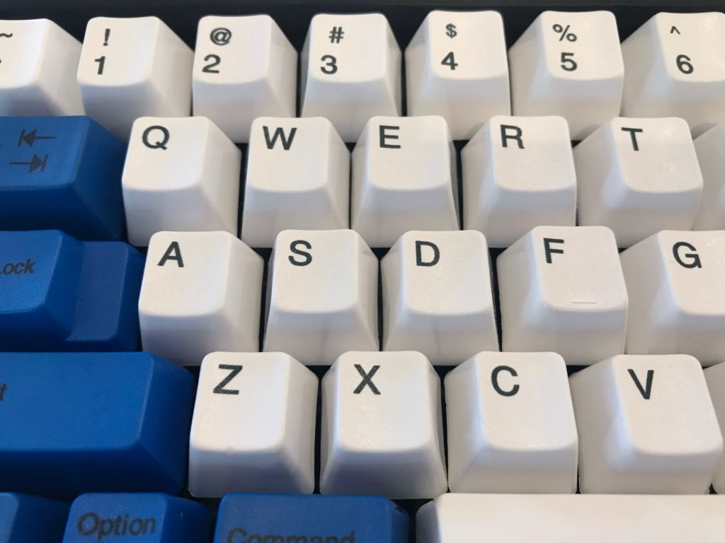 Spacesaver M dye sublimated PBT keycaps in brilliant white with blue ANSI key mod