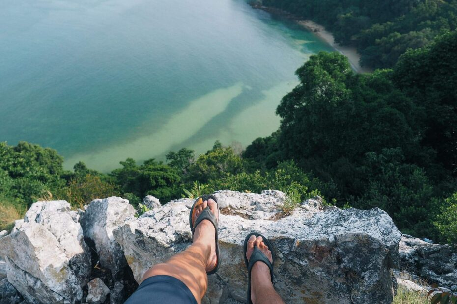 Man standing on a cliff looking downwards