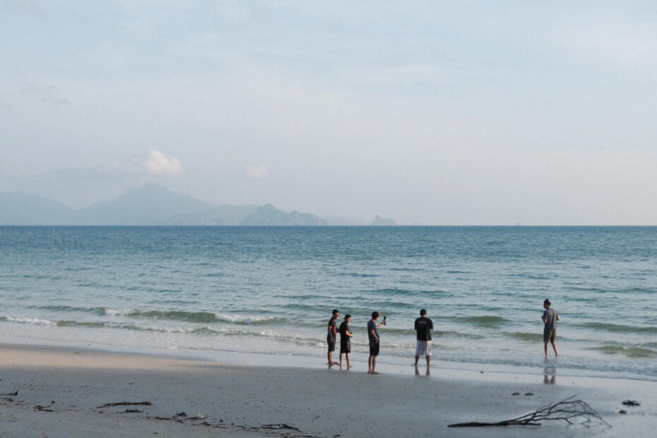 4 guys taking photograph of a man running on the beach