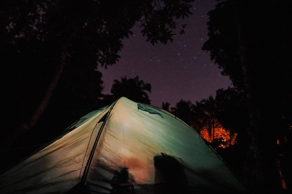Green tent under the night sky in the forest