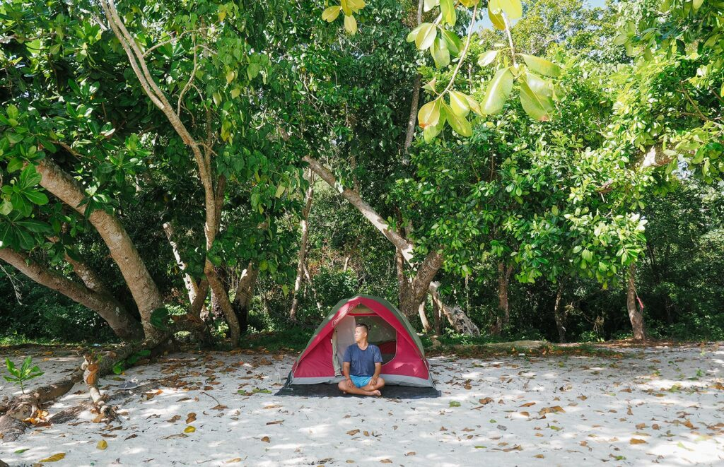 Man sitting in front of a tent on the beach, backed with lush green forest