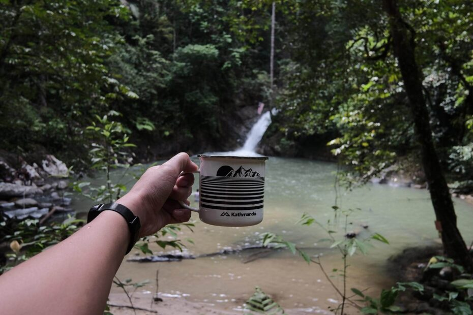 Posing with a mug filling the water from the falls