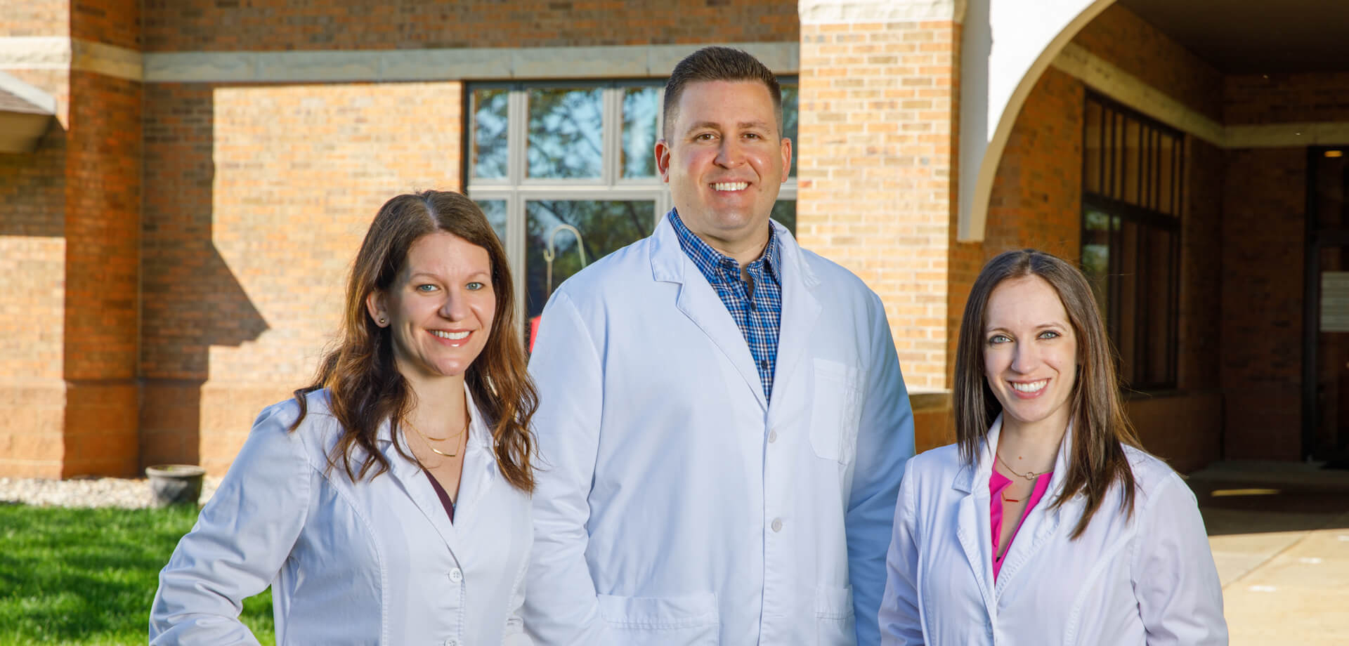 A group photo of doctors Mlodik, Snyder, and Kutzler, standing in front of the main entrance of Point Place Dental