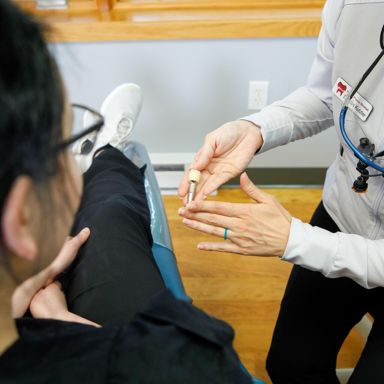 Dr Kutzler, as identified by her name tag, shows a client a dental implant