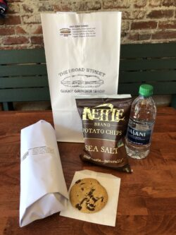 """Image of a bag with 9"""" sandwich, cookie, small bag of chips, and water bottle laying in front of it"""