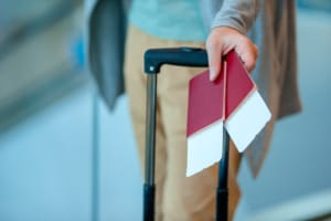man in the airport with his luggage and passports.
