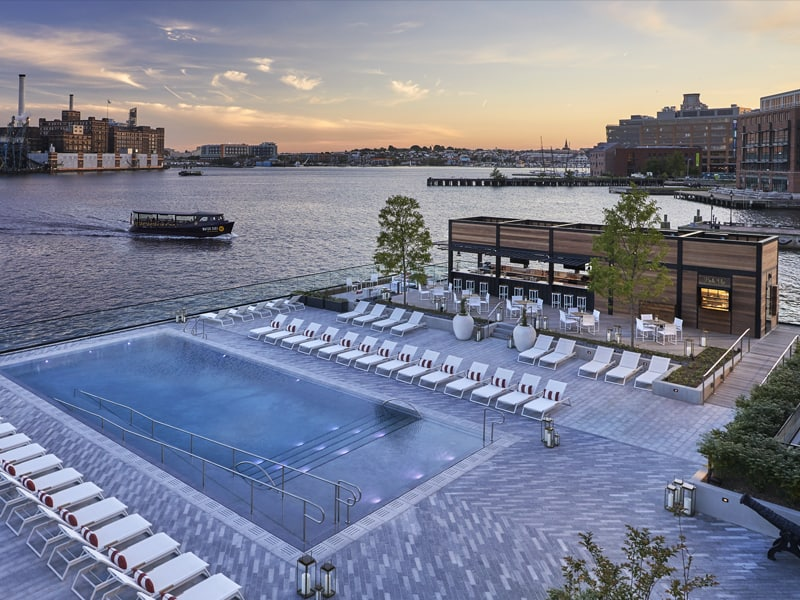 Sagamore Pendry Baltimore pool view at sunset, overlooking water and water taxi