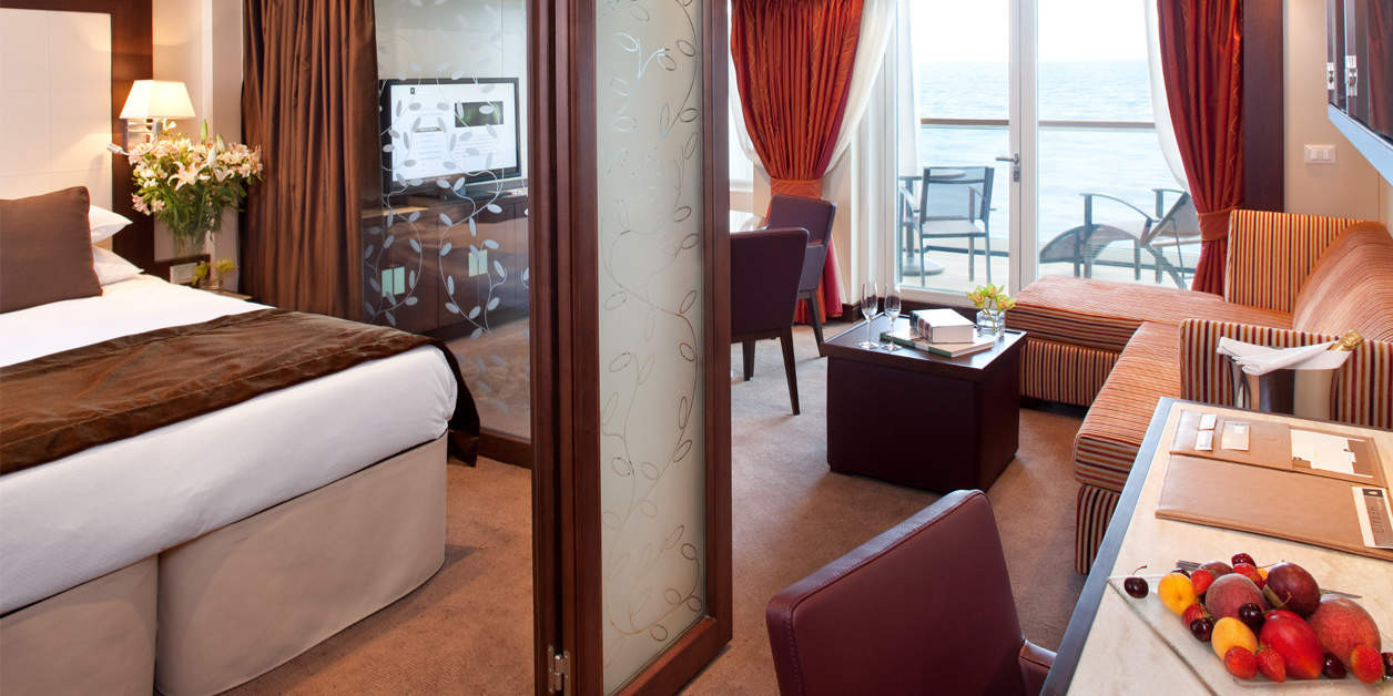 interior view of Seabourn Sojourn penthouse suite with bed, desk, chair, and balcony in view.