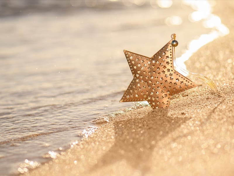 A gold star Christmas ornament stands in the sand on a tropical beach near the ocean.