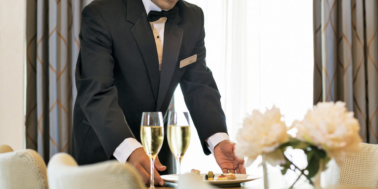cropped photo of butler serving food and champagne on Regent ship.