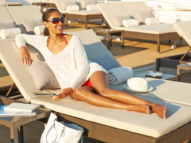 African American woman smiling while lounging on the deck of a Seabourn cruise ship.