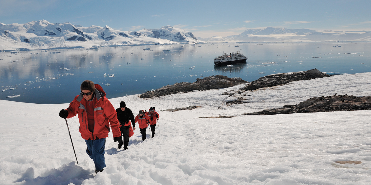 Silversea Cruises' Guests hiking in Antarctica, with ship in background.