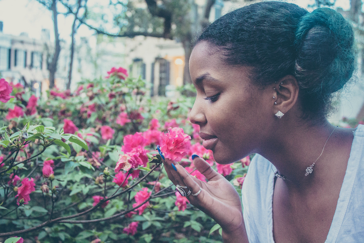 Image of a girl smelling a flower