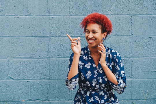Image of a woman with red hair pointing at a blue wall and smiling