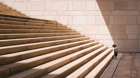Image of a toddler facing a giant staircase
