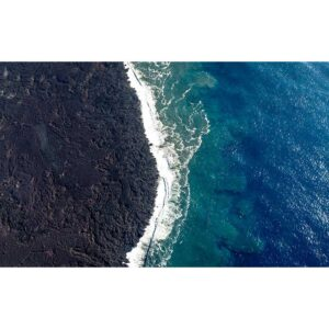 aerial photo of black lava and ocean