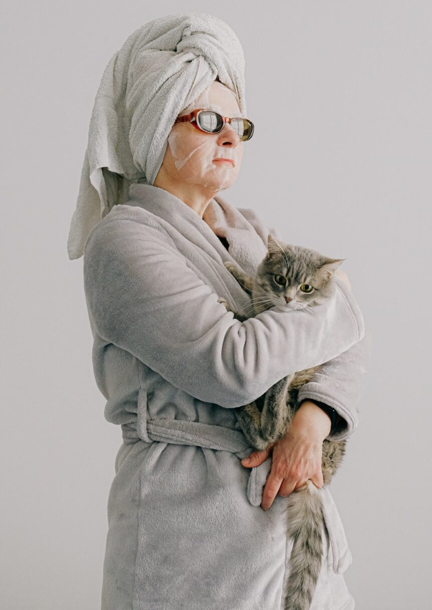 Woman holding a cat after completing her anti-aging skin routine