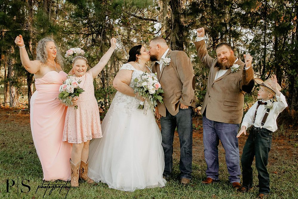 Wedding couple kissing while relatives are rejoicing on the side