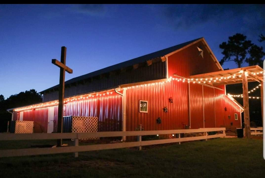 Lit-up barn with a cross