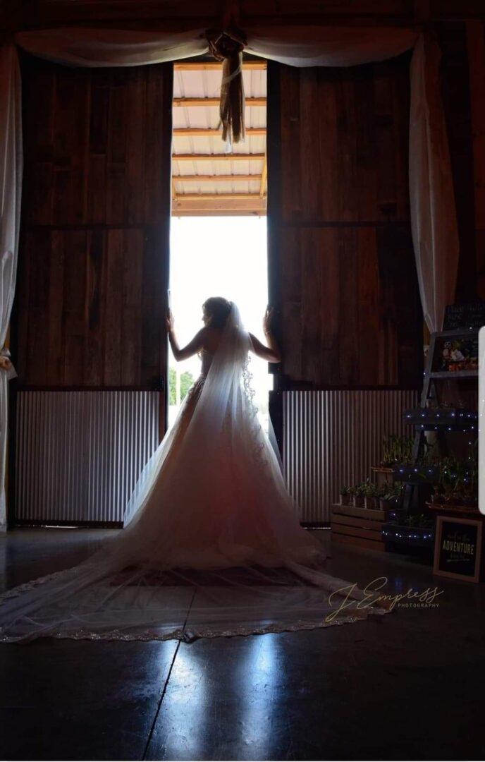 Back view of a wedding bride opening the doors of the barn