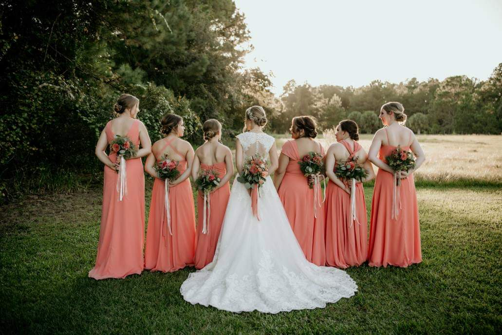 Bride with her bridesmaids turning their backs on the camera