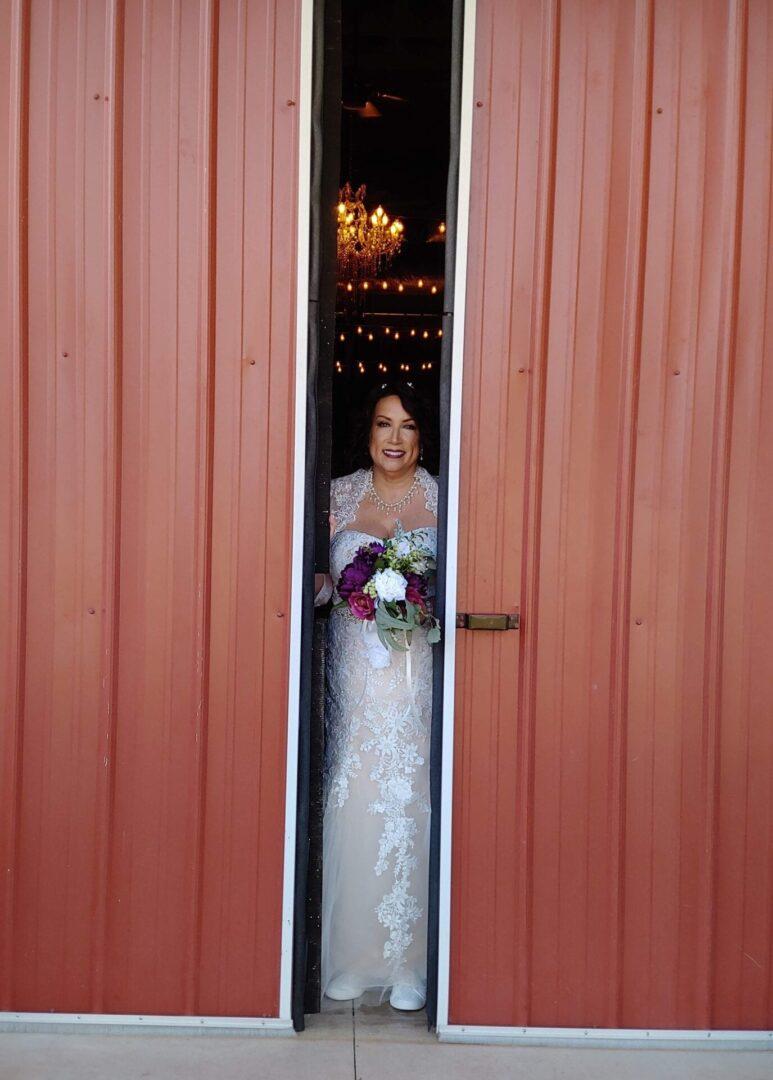 Bride seen through the gap between the barn's doors