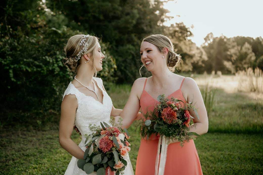 Bride laughing with a bridesmaid in an orange dress