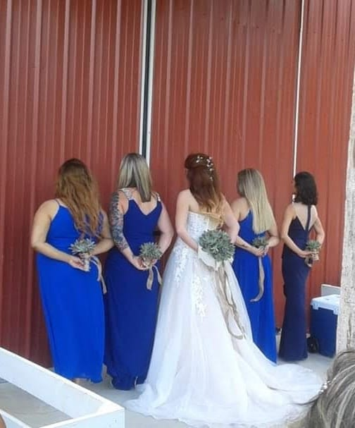 Bride and bridesmaids standing on a bard with their back faced on the camera