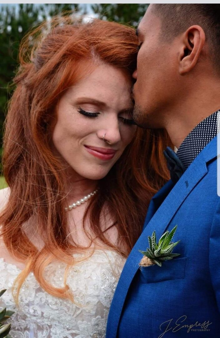 Groom kissing the forehead of his bride