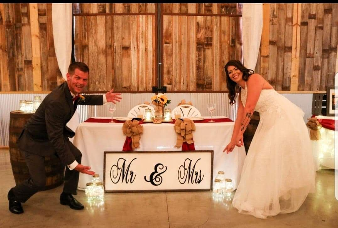 Wedding couple rejoicing in front of the reception table