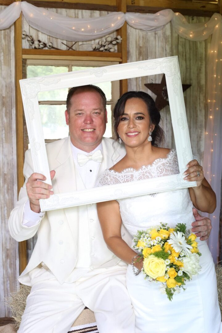 Wedding couple smiling while holding a white picture frame