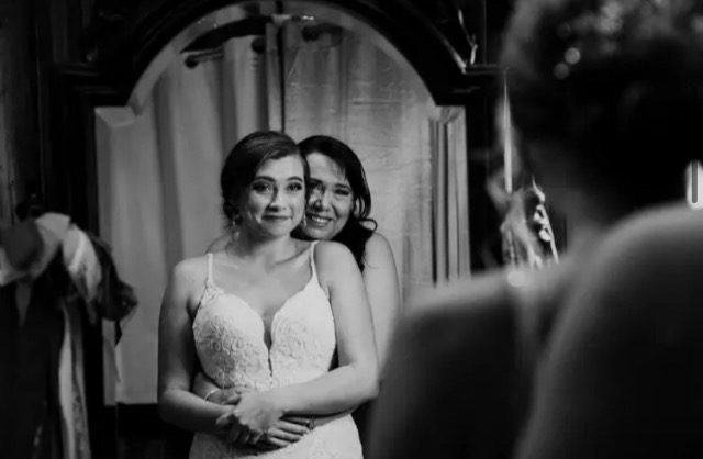 Wedding bride being hugged by her mom while looking on a mirror