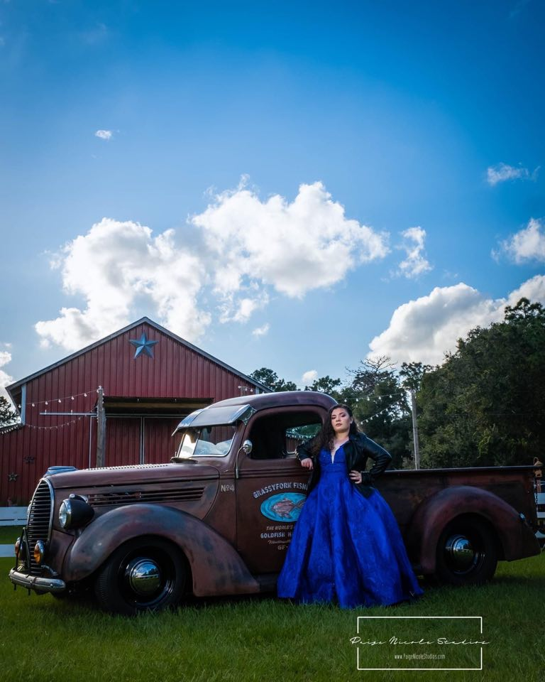 Alexa wearing a blue dress while standing in front of a barn