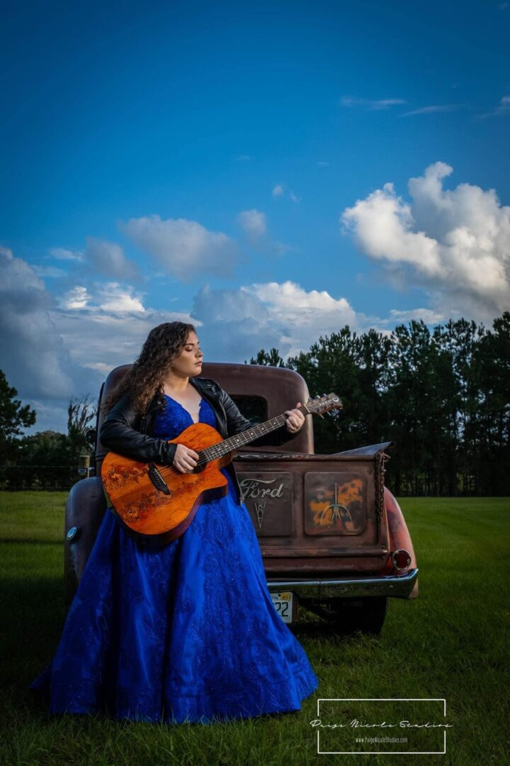 Alexa wearing a blue dress while sitting on vintage truck and playing the guitar