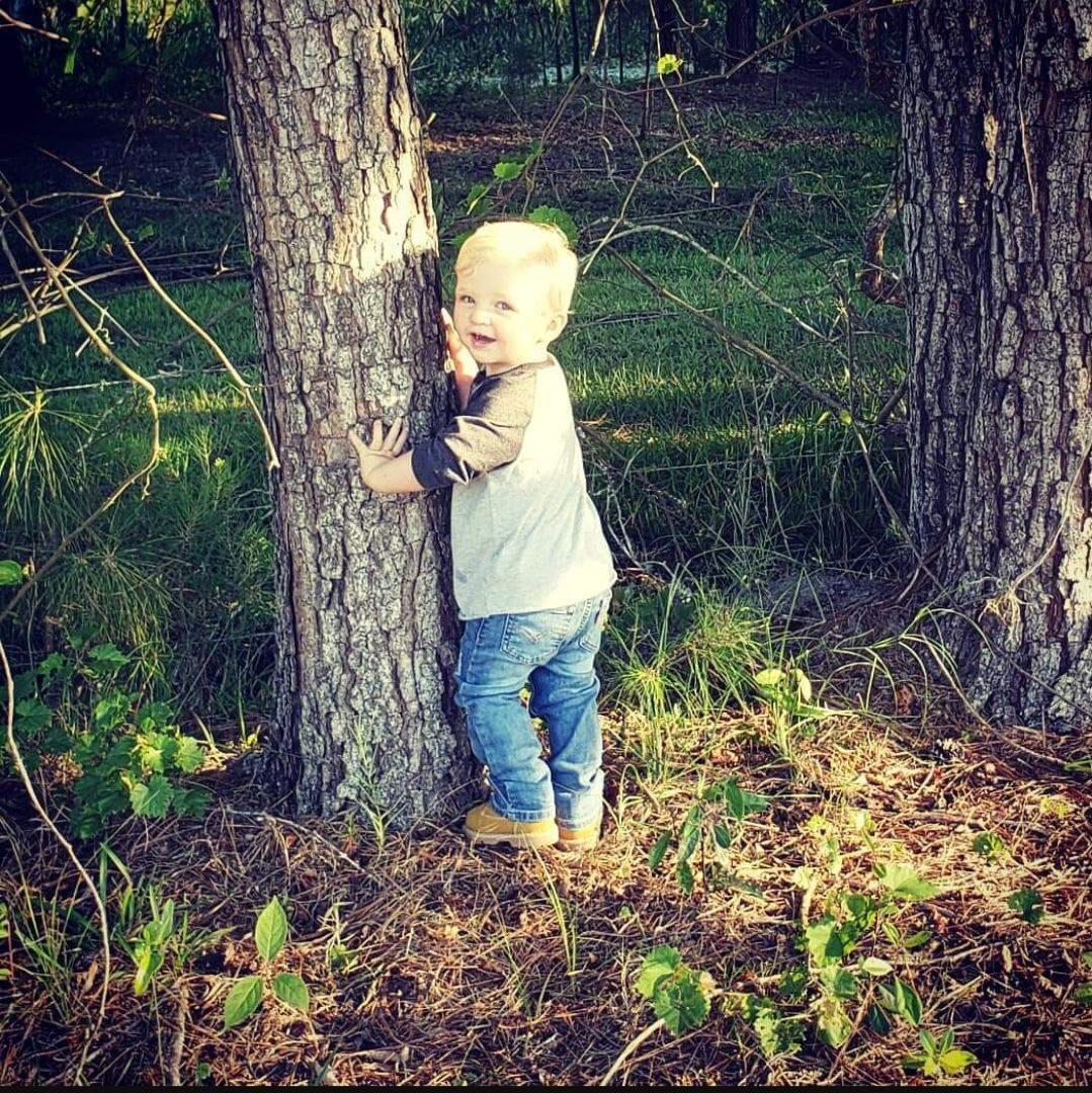 Boy on bare feet beside a tree trunk
