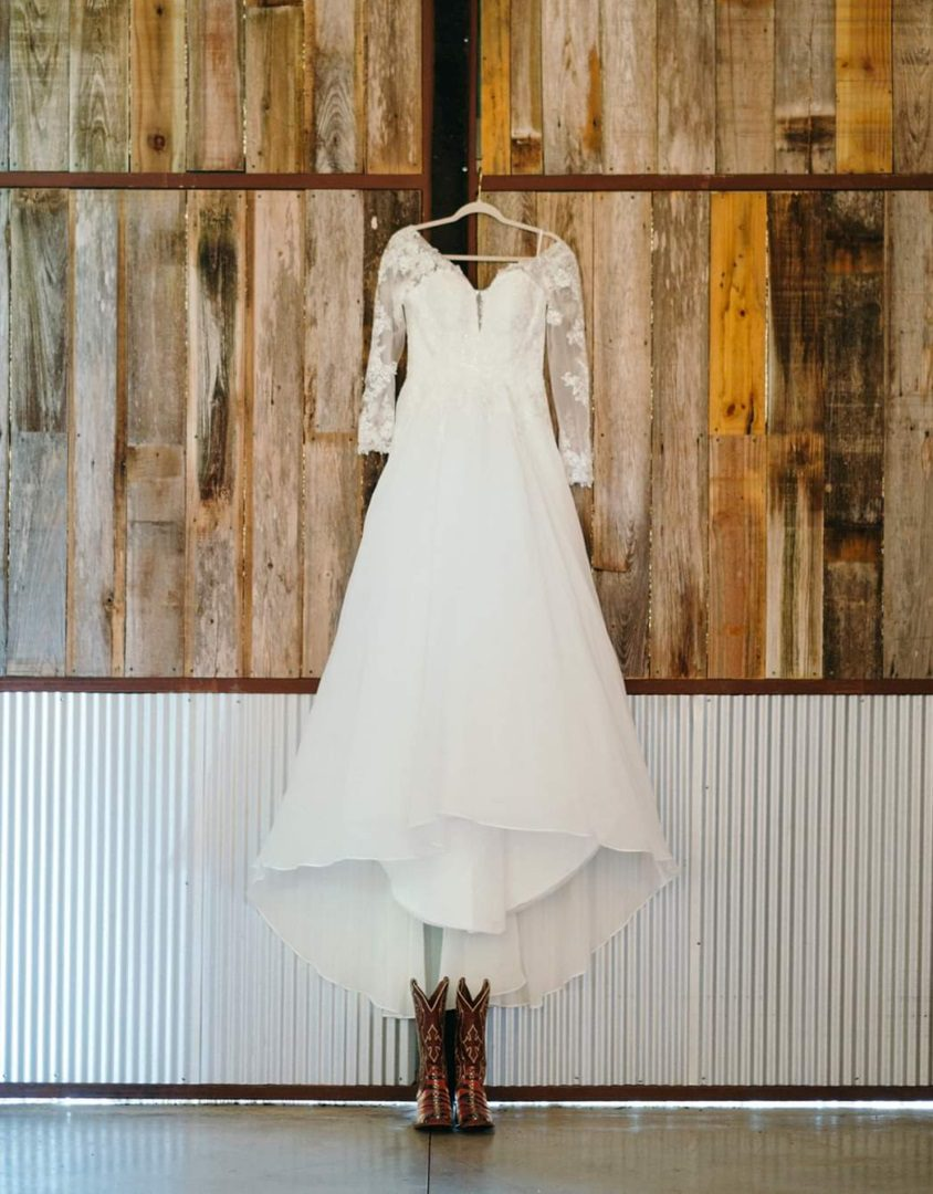 White, long-sleeved wedding dress with cowboy boots