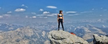 Têra Kaia ambassador and outdoor woman Cheyenne Sukalski in a Neptune Low Cut basewear top sports bra standing on a peak over Yosemite looking into the valley