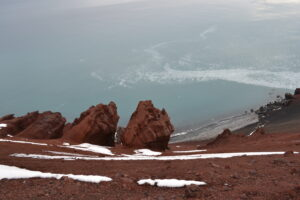 Deacon Peak is a cinder cone with volcanic red rock remnants. Antarctic Kayaking