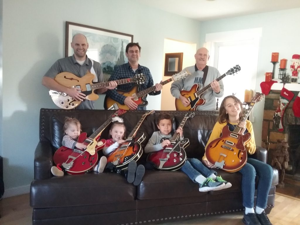 My two sons and four grand children holding Japanese copies of a Gibson 335. I'm holding the only real Gibson.