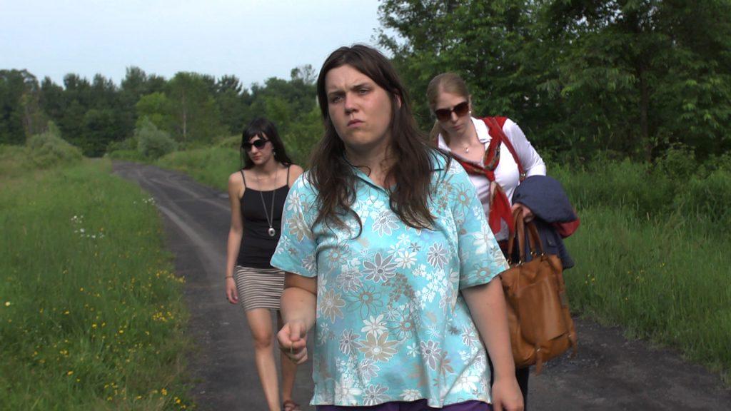 Three women walking down remote road